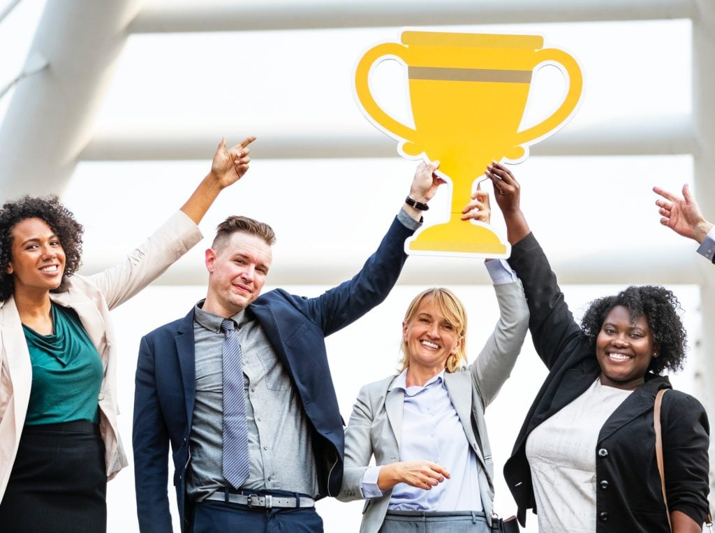 business people raising trophy, achievement, award